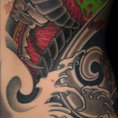 Detail of dragon and phoenix half back and sleeve tattoo